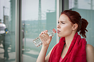 Young athlete taking a break, drinking water - JUNF01003