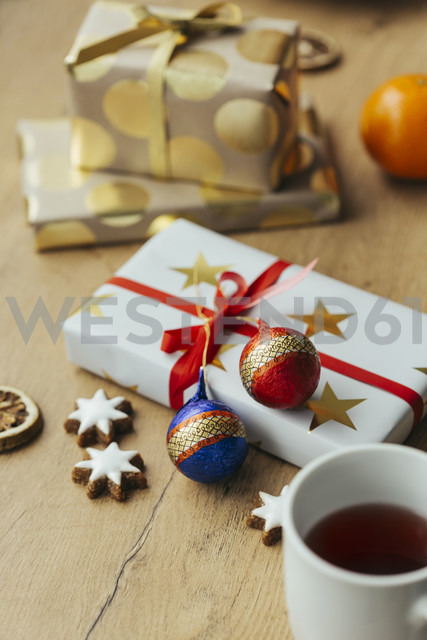 Cup of tea, cinnamon stars and Christmas presents in the background - JHAF00006