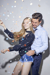 Young couple dancing under shower of confetti - PNEF00184