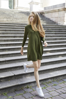 Portrait of young woman wearing green dress walking downstairs - PNEF00199