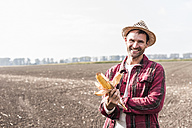 Portrait of smiling farmer on field holding corn cob - UUF11909