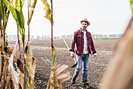 Farmer walking along cornfield - UUF11912