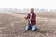 Farmer kneeling on plowed field examining soil - UUF11915