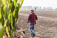 Farmer walking along cornfield - UUF11918