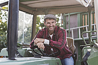 Portrait of confident farmer on tractor - UUF11939