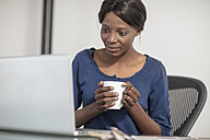 Woman in office with cup of coffee looking at laptop - ZEF14659