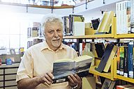 Portrait of senior man in a city library holding book - FRF00569