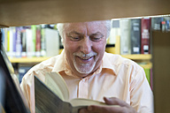 Portrait of smiling senior man in a city library reading book - FRF00572