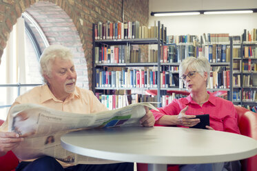 Senior couple with newspaper and e-book in a city library - FRF00578