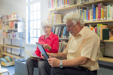 Senior couple with laptop and book in a city library - FRF00581