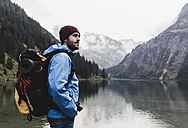Austria, Tyrol, Alps, hiker standing at mountain lake - UUF11944