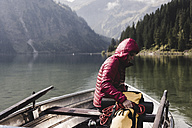 Austria, Tyrol, Alps, woman with backpack in boat on mountain lake - UUF11950