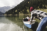 Austria, Tyrol, Alps, couple with rowing boat on mountain lake - UUF11962