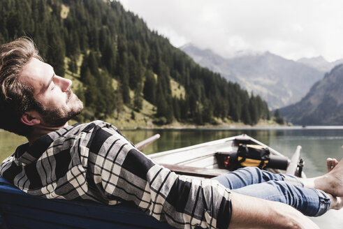 Austria, Tyrol, Alps, relaxed man in boat on mountain lake - UUF11965