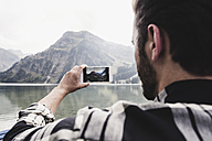 Austria, Tyrol, Alps, man taking cell phone picture of mountainscape - UUF11968