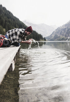 Austria, Tyrol, Alps, man kneeling on jetty refreshing at mountain lake - UUF11974