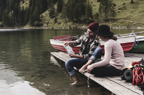 Austria, Tyrol, Alps, couple with map sitting on jetty at mountain lake - UUF11977
