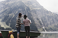 Austria, Tyrol, Alps, couple with map standing at mountain lake - UUF11980