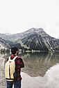 Austria, Tyrol, Alps, hiker standing at mountain lake - UUF11983