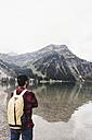Austria, Tyrol, Alps, hiker standing at mountain lake - UUF11983