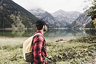 Austria, Tyrol, Alps, hiker standing at mountain lake - UUF11986