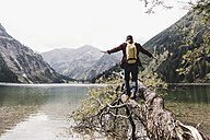 Austria, Tyrol, Alps, hiker balancing on tree trunk at mountain lake - UUF11989