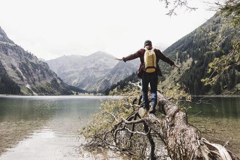 Austria, Tyrol, Alps, hiker balancing on tree trunk at mountain lake - UUF11989