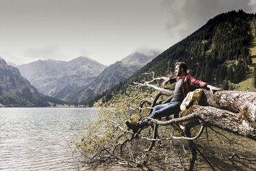Austria, Tyrol, Alps, hiker relaxing on tree trunk at mountain lake - UUF11992