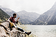 Austria, Tyrol, Alps, hiker on tree trunk at mountain lake using cell phone - UUF11995