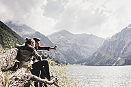 Austria, Tyrol, Alps, couple sitting on tree trunk at mountain lake taking selfie - UUF11998