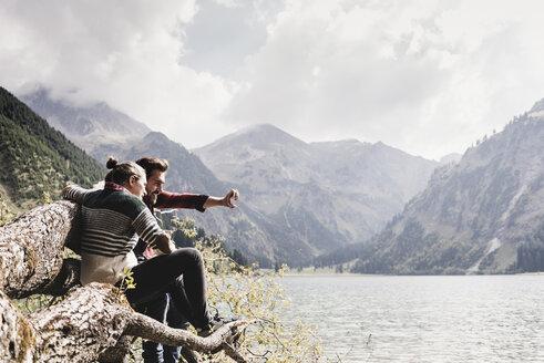 Austria, Tyrol, Alps, couple sitting on tree trunk at mountain lake taking selfie - UUF11998