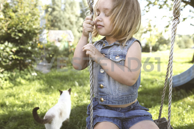 Little girl sitting on swing in the garden - KMKF00020