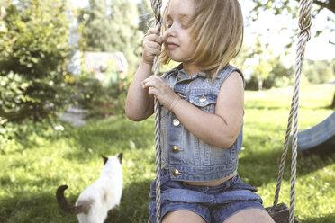 Little girl sitting on swing in the garden - KMKF00020