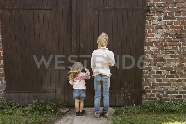 Back view of brother and his little sister standing in front of wooden door - KMKF00029