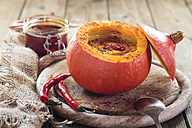 Creamed vegan pumpkin soup with chili in hollowed Hokkaido pumpkin on wooden board - SBDF03335