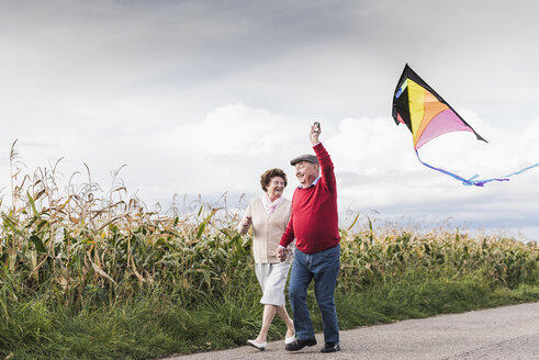 Happy senior couple with kite in rural landscape - UUF12002