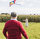 Senior couple flying kite in rural landscape - UUF12005