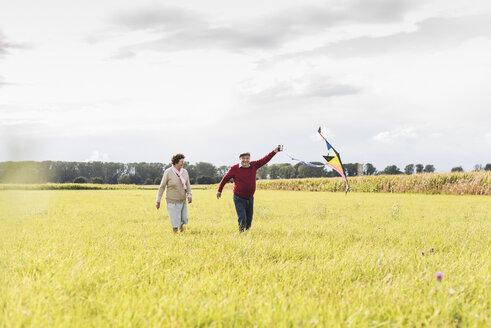 Happy senior couple flying kite in rural landscape - UUF12008