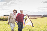 Happy senior couple walking with kite in rural landscape - UUF12011