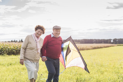 Happy senior couple walking with kite in rural landscape - UUF12011