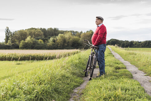 Senior man with bicycle in rural landscape - UUF12014