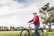 Senior man pushing bicycle in rural landscape - UUF12017