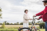 Senior man and woman with bicycles meeting in rural landscape - UUF12020