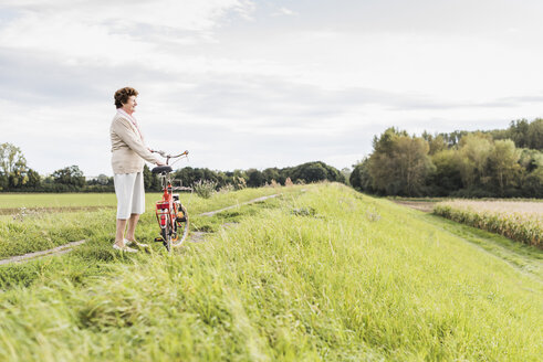 Senior woman with bicycle in rural landscape - UUF12023