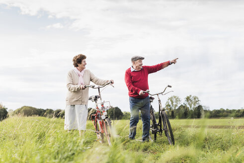 Senior couple with bicycles in rural landscape - UUF12026