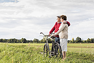 Senior couple with bicycles embracing in rural landscape - UUF12029