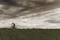 Senior couple with bicycles in rural landscape under cloudy sky - UUF12032