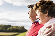 Senior couple embracing in rural landscape - UUF12035