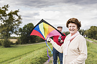 Portrait of smiling senior couple with kite in rural landscape - UUF12044