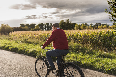 Senior man riding bicycle on country lane - UUF12050